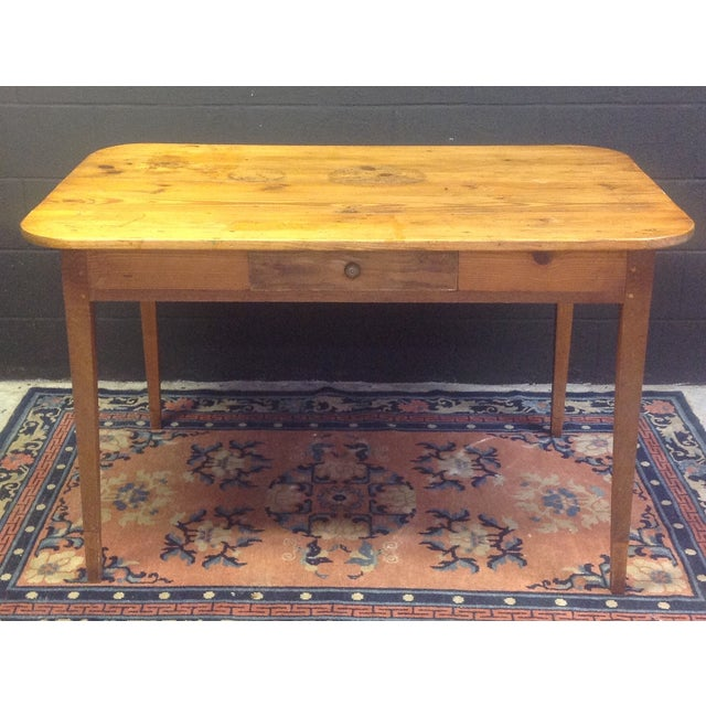 This French pine worktable is from the early 20th century. It has a frieze drawer, decorative carved sides and tapered...