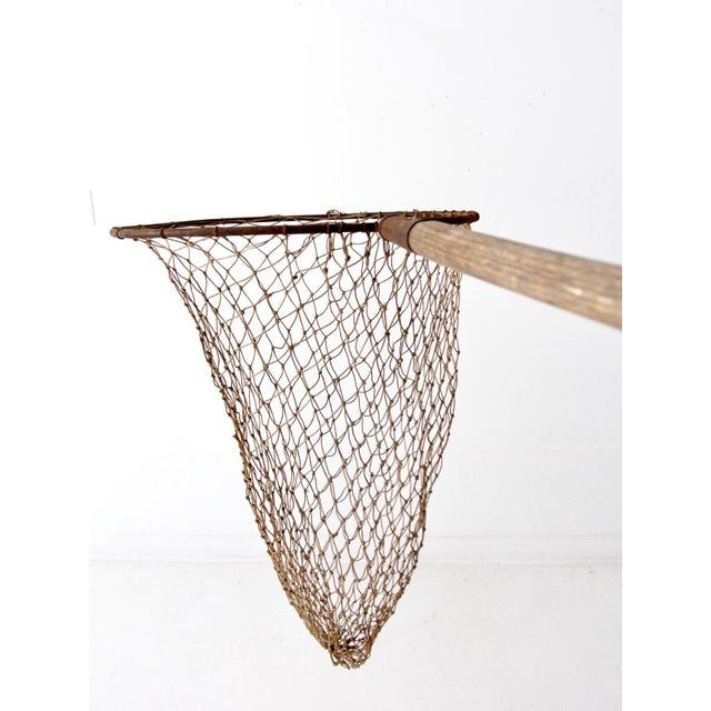 This is an antique fishing net on pole. The large hand held net features a wooden pole and metal frame with large woven...