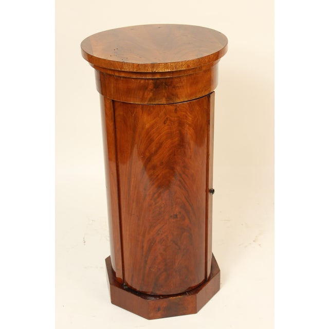 Continental Napoleon III flame mahogany cylinder cupboard / pedestal, with a book matched flame mahogany top, 3rd quarter...