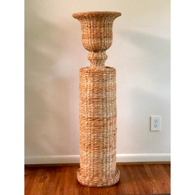 This is a fabulous urn shaped planter on a pedestal base made of metal with a woven rattan exterior.