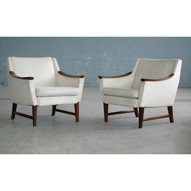 Quite a charming pair of Danish lounge chairs. The design is very interesting showing design cues from both Ole Wanscher...