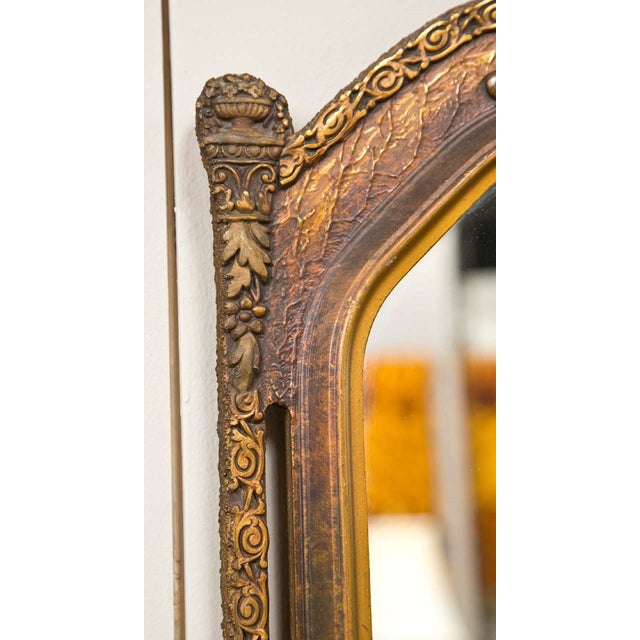 A pair of gilt gold wooden wall mirrors. Each has a central mirror and a frame in carved gold gilt, both with open sides.