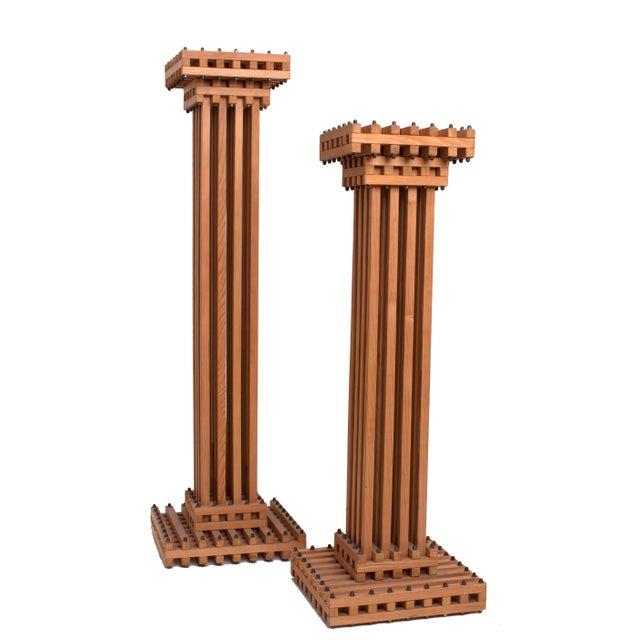 An intricate pair of sculptural, geometric lattice column pedestals in oak with decorative steel bolts, Cubist in style....