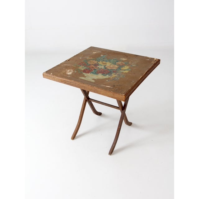A vintage folding table circa 1930s. The small card table features a paper covered table top adorned with a painted print...