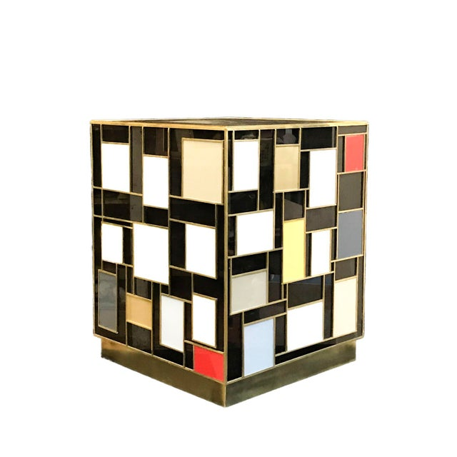 This little gem of side table is inspired from the colorful works of Mondrian. Black glass encases the wooden frame....