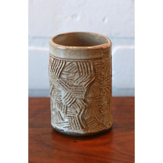 Hand built ceramic stoneware vessel with textured .markings on the exterior of the piece. The piece is marked.