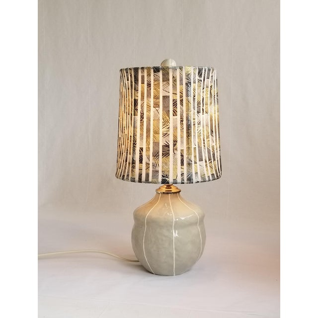 Handmade ceramic lamp glazed in soft gray with raised white stripes. It's chubby, acorn shape is just the right size to be...