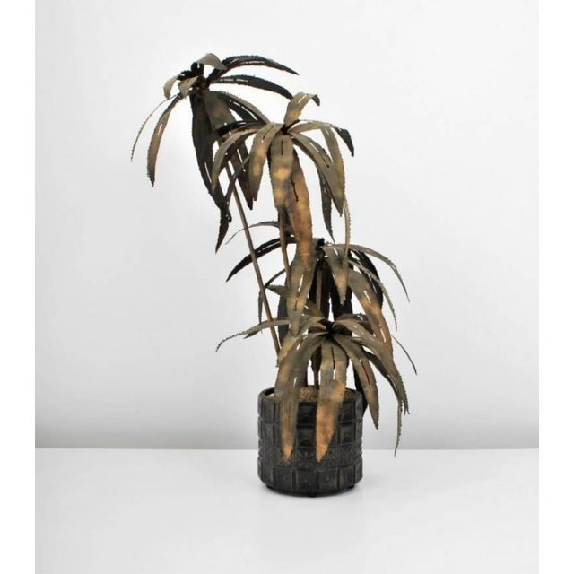 A spectacular illuminated torch-cut palm tree sculpture in a Brutalist Paul Evans style pot, circa 1970. We are unsure the...