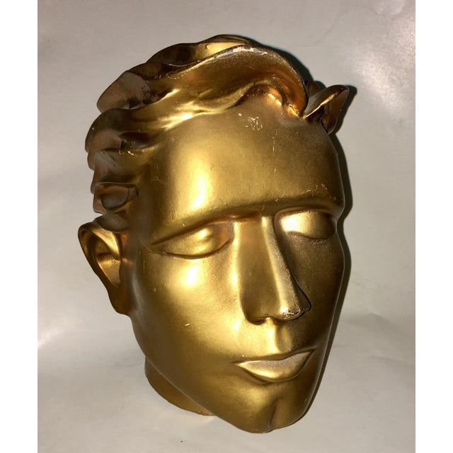 A very beautiful highly stylized fiberglass man's head with a gold finish. A great sculpture piece. A few places where the...