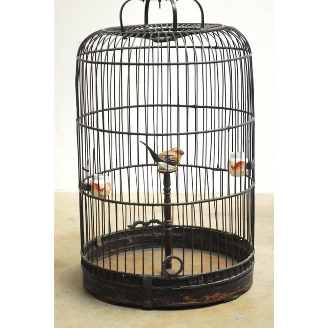 Impressive antique Chinese domed bamboo bird cage with a functioning sliding door. Features a dark lacquer finish and a...