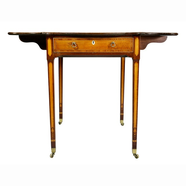 Drop leaf table with rectangular top and serpentine drop leaves over a drawer raised on square tapered legs with casters.