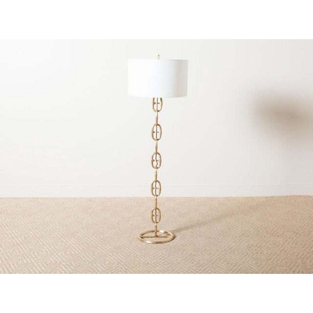 Brass interlocking chain floor lamp. White paper shade. Cloth-wrapped cord.