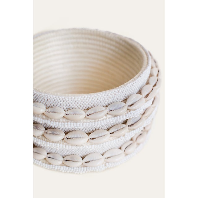 "Hand-Beaded Bucket Cowrie Accents 4.5"" x 7"" Our hand-beaded products are crafted with delicate detail by our artisan..."