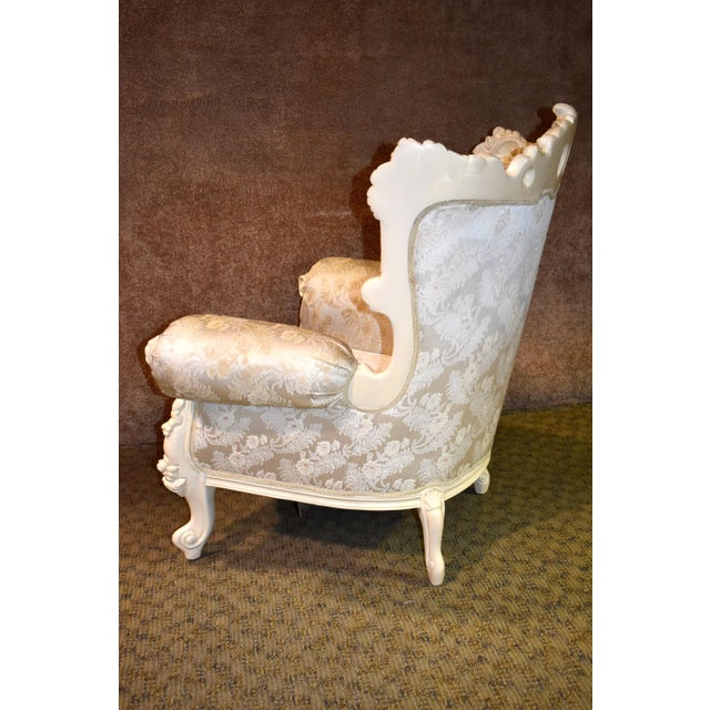 Ornate Bergere Chair has a Renaissance Style. Carved wood frame, rolled arms, and patterned fabric. The base has an...
