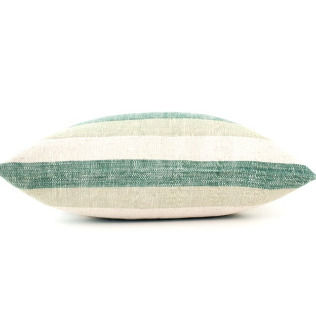 Striped cotton pillow with invisible zipper across bottom. Handwoven using organic cotton and natural dyes in Laos. Insert...