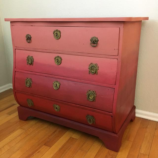 Dramatic color presented in a smoldering, understated way. This antique bombe-style chest bows out gracefully in the...