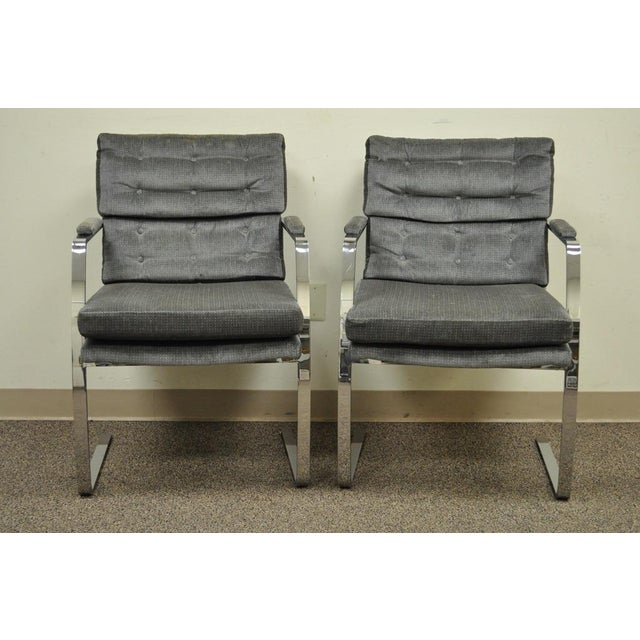 Item: Pair of Vintage Mid Century Modern Chrome Plated Steel Cantilevered Arm Chairs. The chairs have a sturdy and...