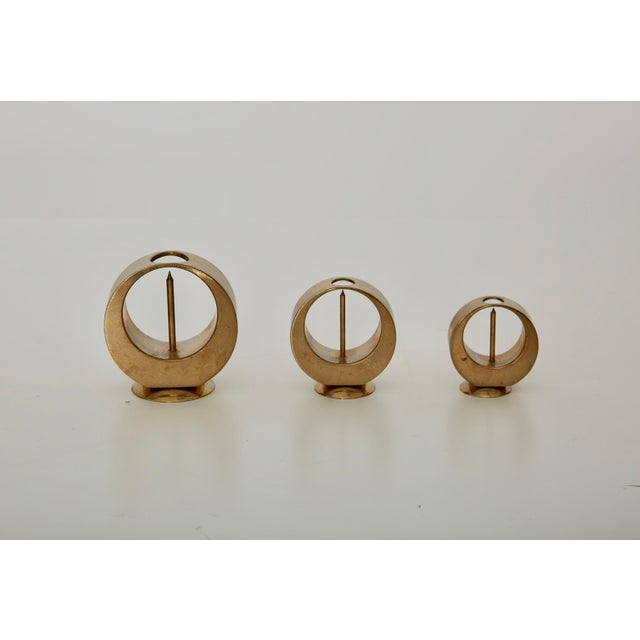 A set of three elegant and very rare midcentury brass candleholders, by Artur Pe Kolbäck. In very good vintage condition...