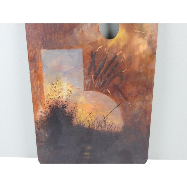 Painting on wood artist palette featuring cat tails and moonlit lake. Unsigned and unframed. Edge wear, a few small scuff...