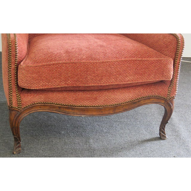 Louis XV style wing chair with nail head trim and textured upholstery.