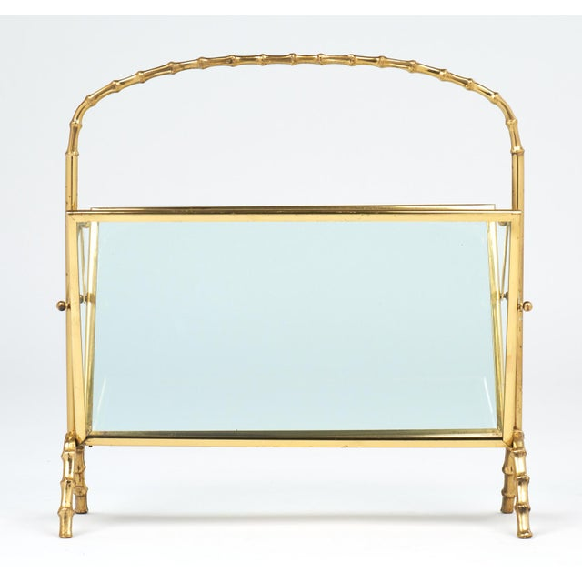 Vintage Maison Baguès faux bamboo French magazine stand. This brass frame stand features a bamboo style handle and...
