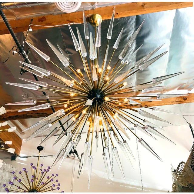 Italian Sputnik chandelier shown in clear Murano glass shards with black enameled centre on natural brass frame designed...
