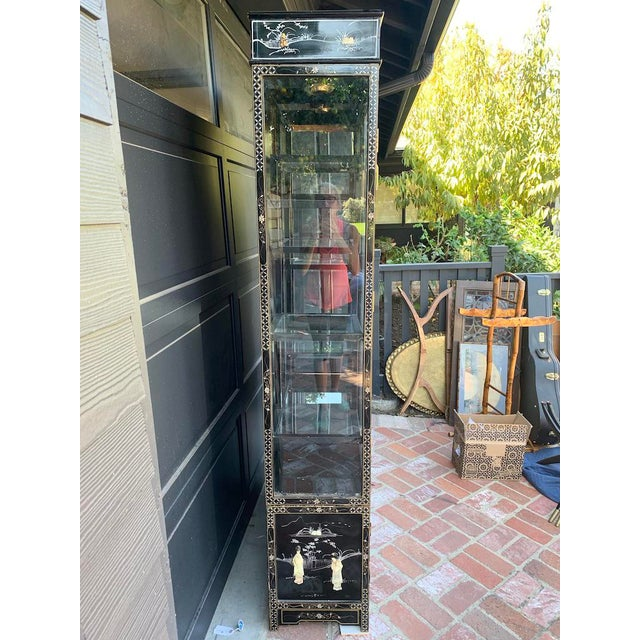 Black laquered China Cabinet wiht mother of pearl inlay of scnes. Mirrored glass shelving. Cabinet can light up. 2 peices....