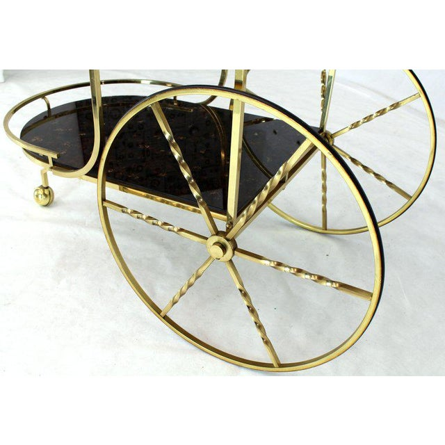 """Decorative mid-century modern two-tier bar tea serving cart on large carriage style brass wheels. The lower level is 12"""" H."""