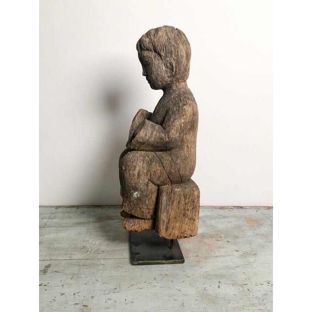 A late 19th early 20th Century South East Asian fragment wood carving of a seated child, circa 1900.