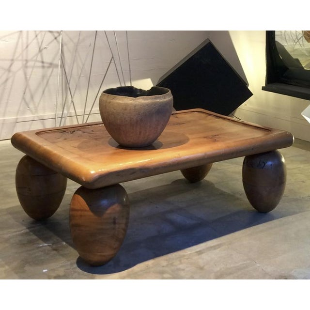 Brutalist coffee table with awesome olive shaped leg.