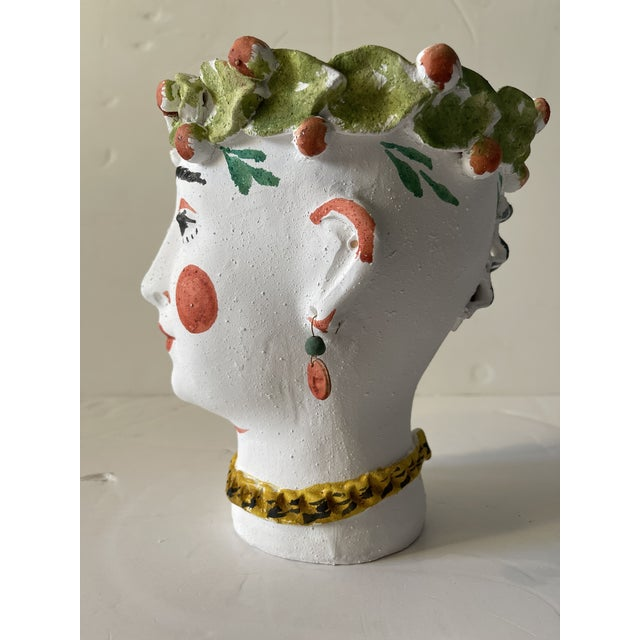 Made in Spain of rough Terra Cotta and painted with natural dyes. Adorned with a flowered head dress and unique earrings....