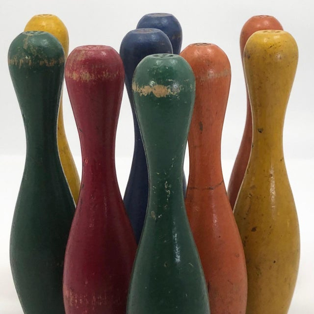 A charming set of vintage painted wood toy bowling pins or skittles in yellow, red, orange, green and blue. Great in a...