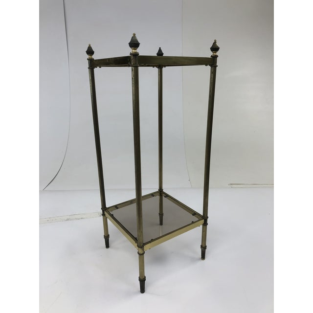 Mid century brass two tier accent table. Beautiful finials on all four posts. Two tiers with smoked glass shelves. Light...