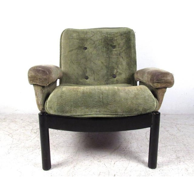 This uniquely designed vintage chair features a low slung style, complete with upholstered armrests, black lacquered...