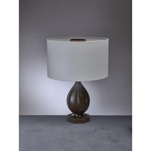 A metal table lamp by Danish designer Ib Just Andersen (1884-1943). The lamp is made of Disko metal; an alloy of lead and...
