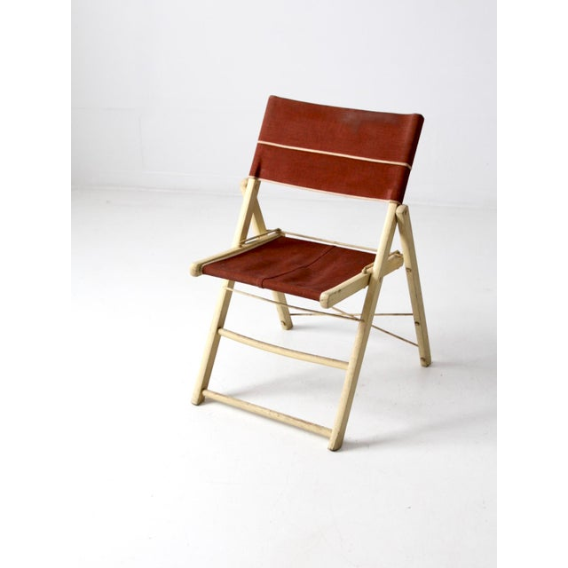 This is a mid-century folding chair. The cream painted wood frame chair features a russet brown twill canvas seat and back...