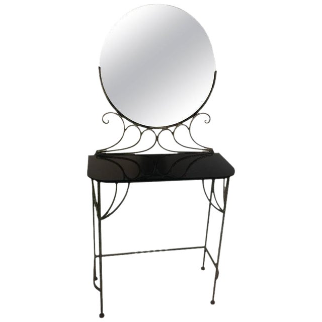 Graceful 1930s wrought iron vanity with round mirror and original black glass top. Original round mirror on top rests in...