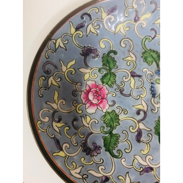 Asian floral design bowl with brass wrap on back. Marked with red characters and Macau.
