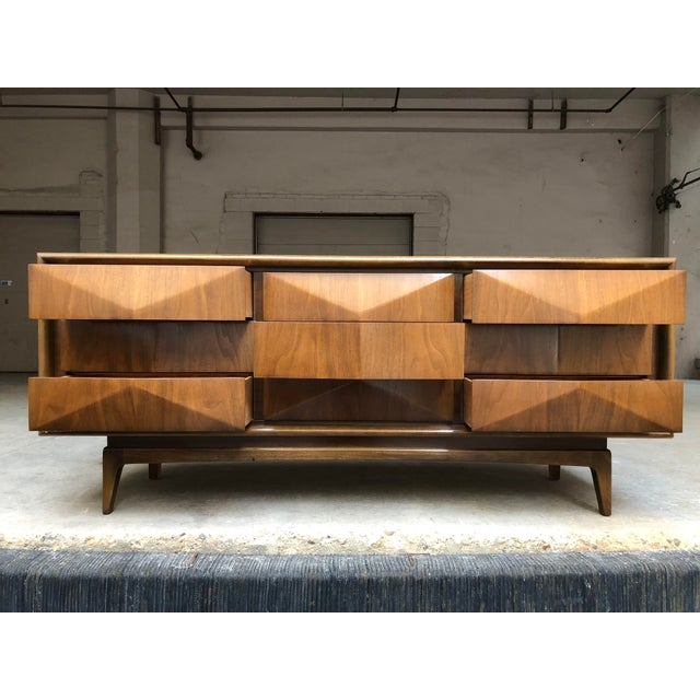 Iconic diamond-front nine drawer lowboy dresser. Constructed of solid walnut, this breathtaking mid-century relic features...