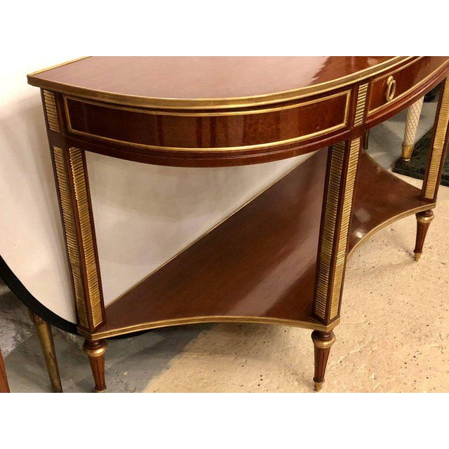 Pair of demilune mahogany bronze-mounted Russian neoclassical consoles with inverted lower shelves. This fine custom...