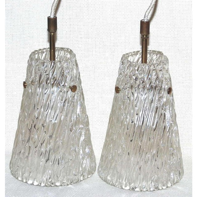 A pair of pendants by Orrefors. Handblown clear textured glass with brass hardware. Designed for one Edison style bulbs...