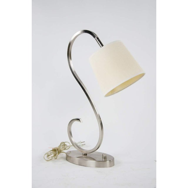 "Modern design meets simple elegance with this modern brushed nickel desk lamp. This piece features a unique ""S"" form,..."