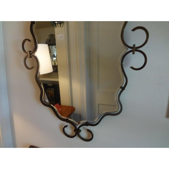 Great French Art Deco hand forged bronze beveled mirror. This mirror appears to be floating inside the iron frame. Late...