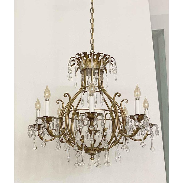 Florentine style crystal and gilt metal chandelier adorned with teardrop crystals. It takes eight candelabra bulbs with...