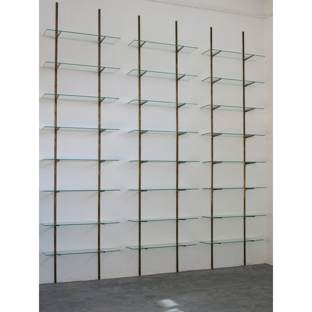 Adjustable brass frame bookcase with glass shelves. Each single unit is composed by two uprights, eight glass shelves and...