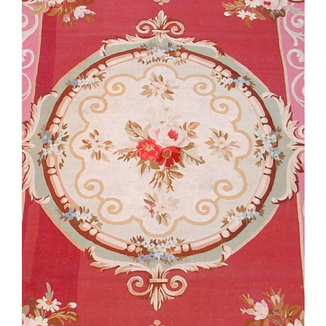 A wonderful scatter-size Aubusson with a cherry red ground and perfect round medallion decorated with scrolls and roses.