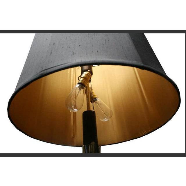 A beautiful floor lamp with an integrated round tabletop and an octagonal black silk shade lined in gold silk. Adorned...