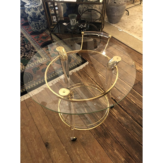 A super glamorous French gold plated brass, lucite and glass round bar cart having an art deco influence. The 3 splayed...