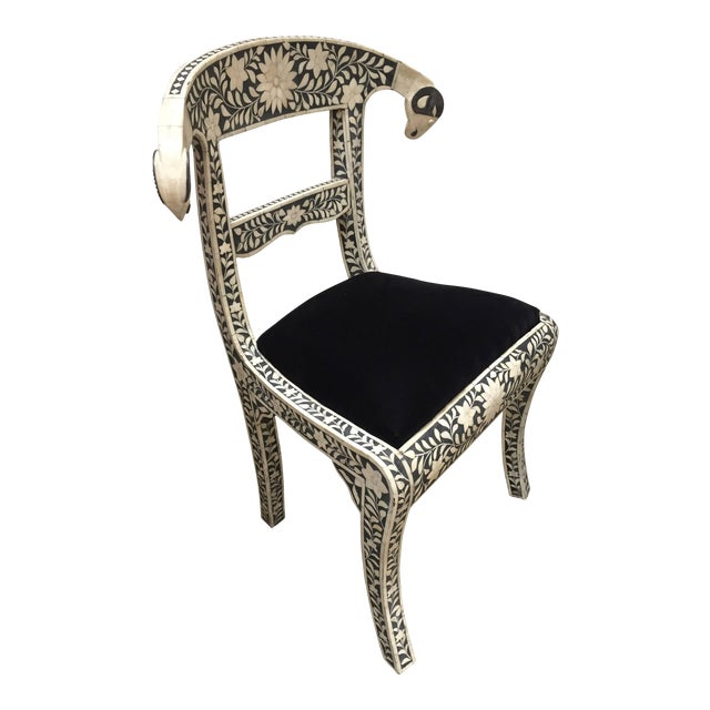 Pair of Anglo-Indian black and white dowry side chairs with ram's head accents. These stunning chairs feature a wooden...