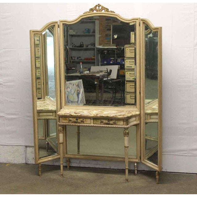 French carved and hand painted wood vanity table with two drawers and an attached tri-fold mirror. It features a delicate...